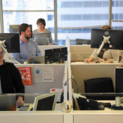 Madeline Hasbrouck, left, and Lauren Crawford work in their new space at Vitality Group, which introduced smaller desks and standing options. (Abel Uribe / Chicago Tribune)